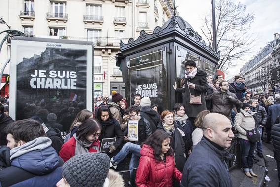 Outside metro Parmentier.  Many of the advertising signs and newspaper kiosks have Je suis Charlie in the place of ads.