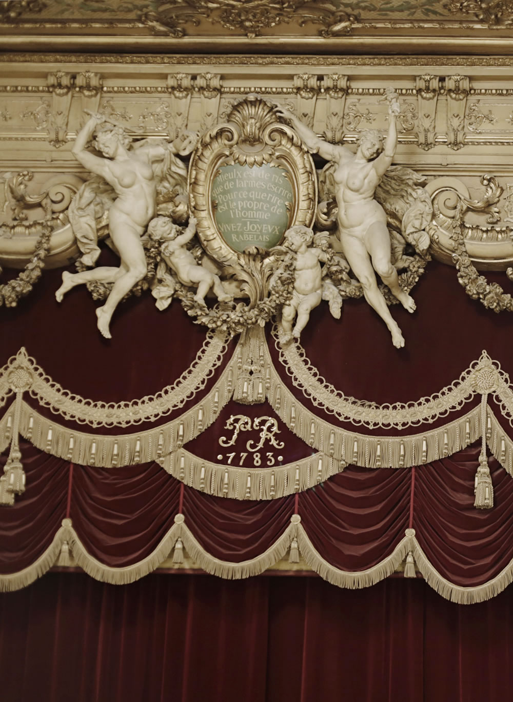 "Frolickers above the curtain at the beautiful Theatre du Palais Royal in Paris.  They float around the famous Rabelais quote, ""Mieux est de ris que de larmes éscrire - Pour ce que rire est le propre de l'homme,"" meaning that laughter belongs to man, and better to laugh than to write down your tears."