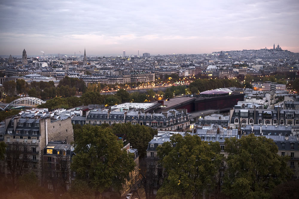 A 6am call-time for a video shoot on the 2nd floor of the Eiffel Tower means you're tired, but so grateful to watch the sun rise over Paris.  On the left you can see the pedestrian bridge Passerelle Debilly, the red building center-right is the back of the Musée du Quai Branly, and up on hill to the right you can see the Sacre Coeur on top of Montmartre.