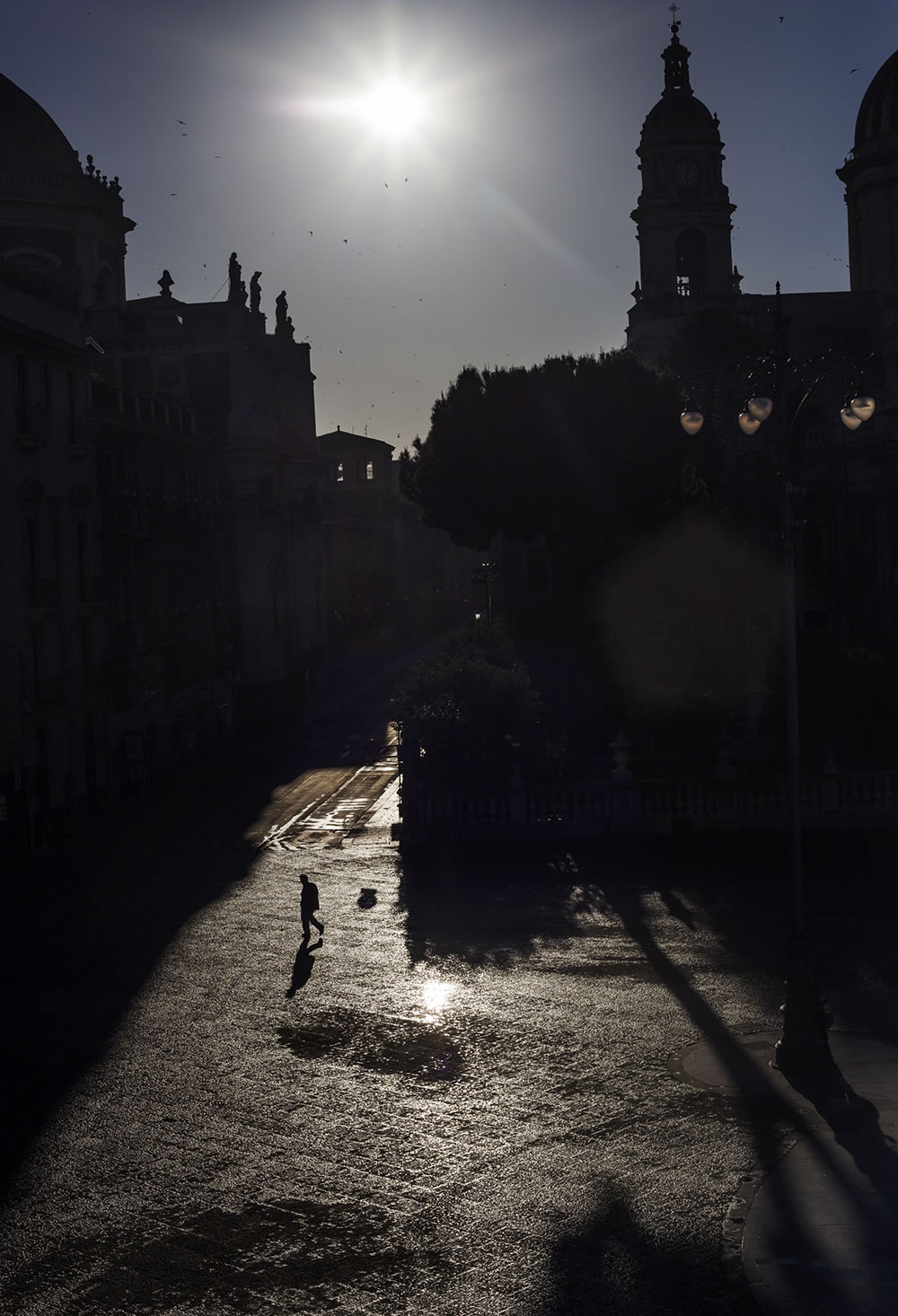 At 7am, through the Baroque shadows in the Piazza del Duomo in Catania, Sicily, the sun is already high and hot.