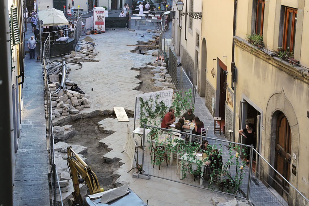 Construction goes on around life, on a warm spring evening in Florence, Italy.