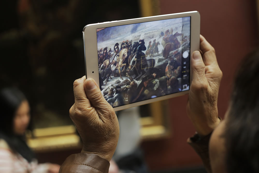A giant painting by Eugène Delacroix being confined to a tablet - the current most popular way to view the masterpieces at the Louvre.