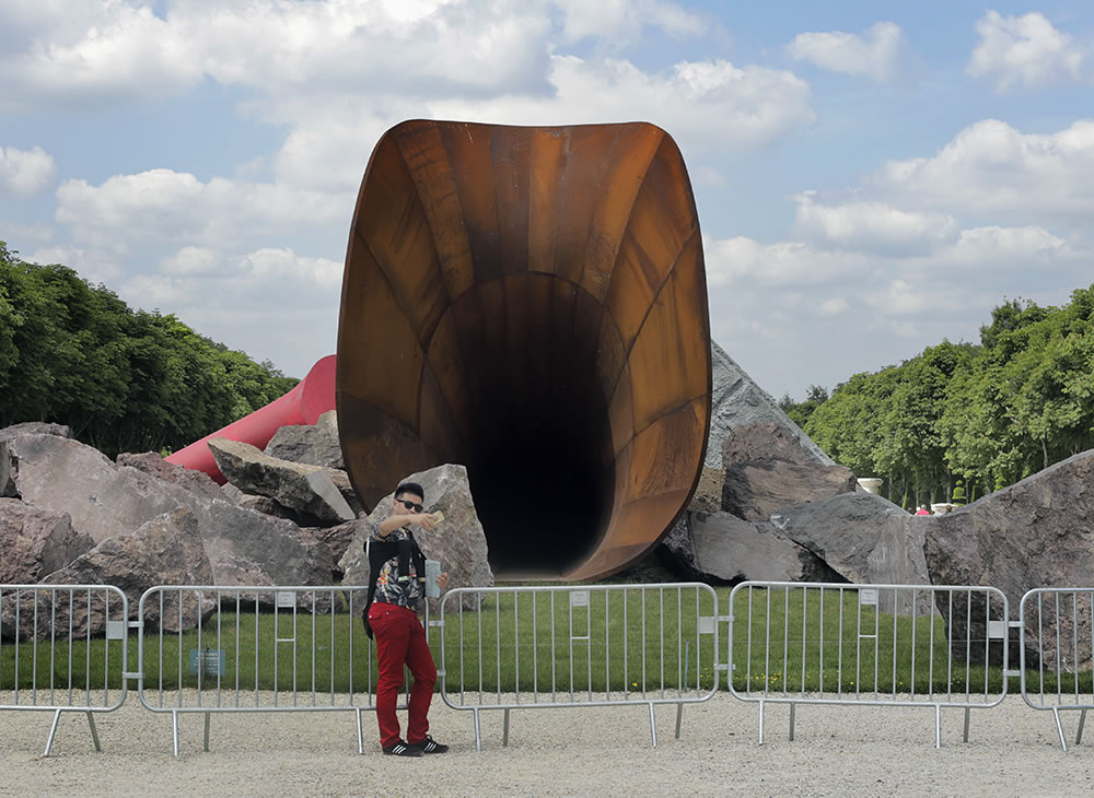 "A man snaps a selfie in front of artist Anish Kapoor's ""Dirty Corner"" sculpture, currently being installed in the gardens at the Chateau de Versailles.  Kapoor is Versaille's invited artist this year, and his exhibition will run from June 9th to November 1st, which gives it time to be in the background of thousands of selfies."