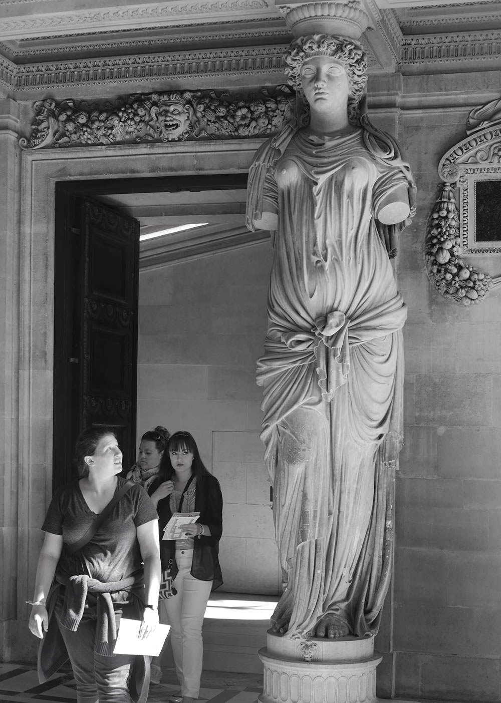 Visitors entering the Caryatid room at the Louvre, whose doorway is flanked by four female figures (the caryatids: female figures serving as architectural support) sculpted by Jean Goujon in 1550.