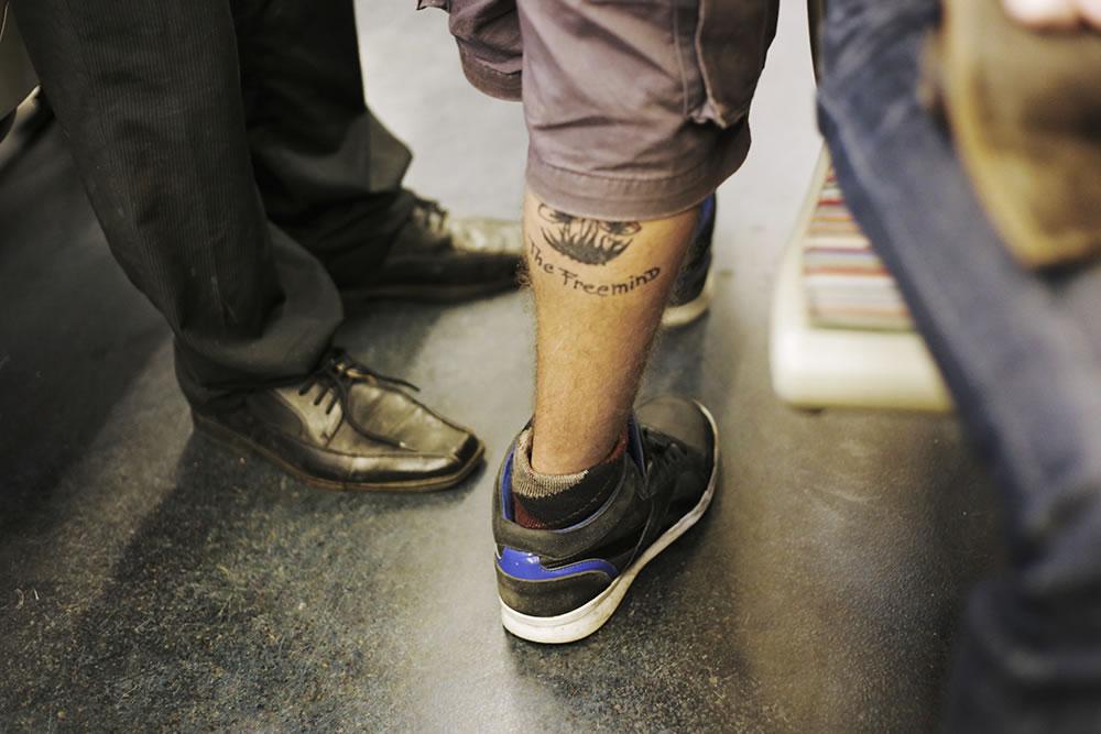 A free spirit in argyle socks walks through a line 5 metro car in Paris.