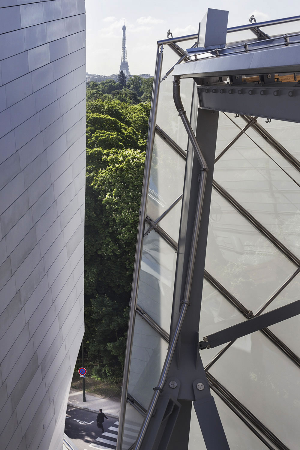 A man leaves the Fondation Louis Vuitton, between what its architect Frank Gehry describes as an iceberg and a glass sail.  The foundation, whose mission is to promote and support contemporary artistic creation, opened to the public in October, 2014 just outside of Paris at the edge of the Bois de Boulogne.