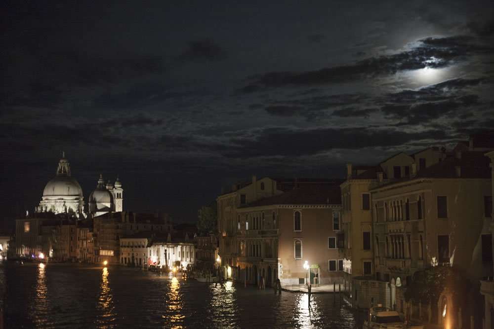 Walking over the Accademia Bridge in Venice, Italy on a full-moon night, looking towards the Peggy Guggenheim museum and the Basilica di Santa Maria della Salute (Saint Mary of Health).