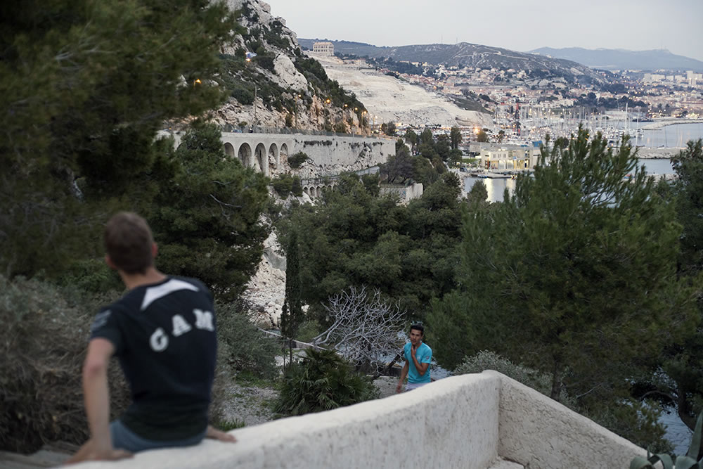 Joggers reach the top of the hill in L'Estaque, a district of Marseille, France that used to be a small fishing village which inspired painters like Cézanne, Renoir and Braque around the turn of the last century, pre-industrialization.