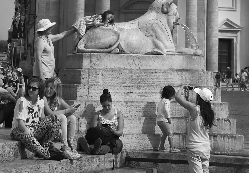 Romans and tourists hanging out at Piazza del Popolo on a summer afternoon in Rome, Italy.