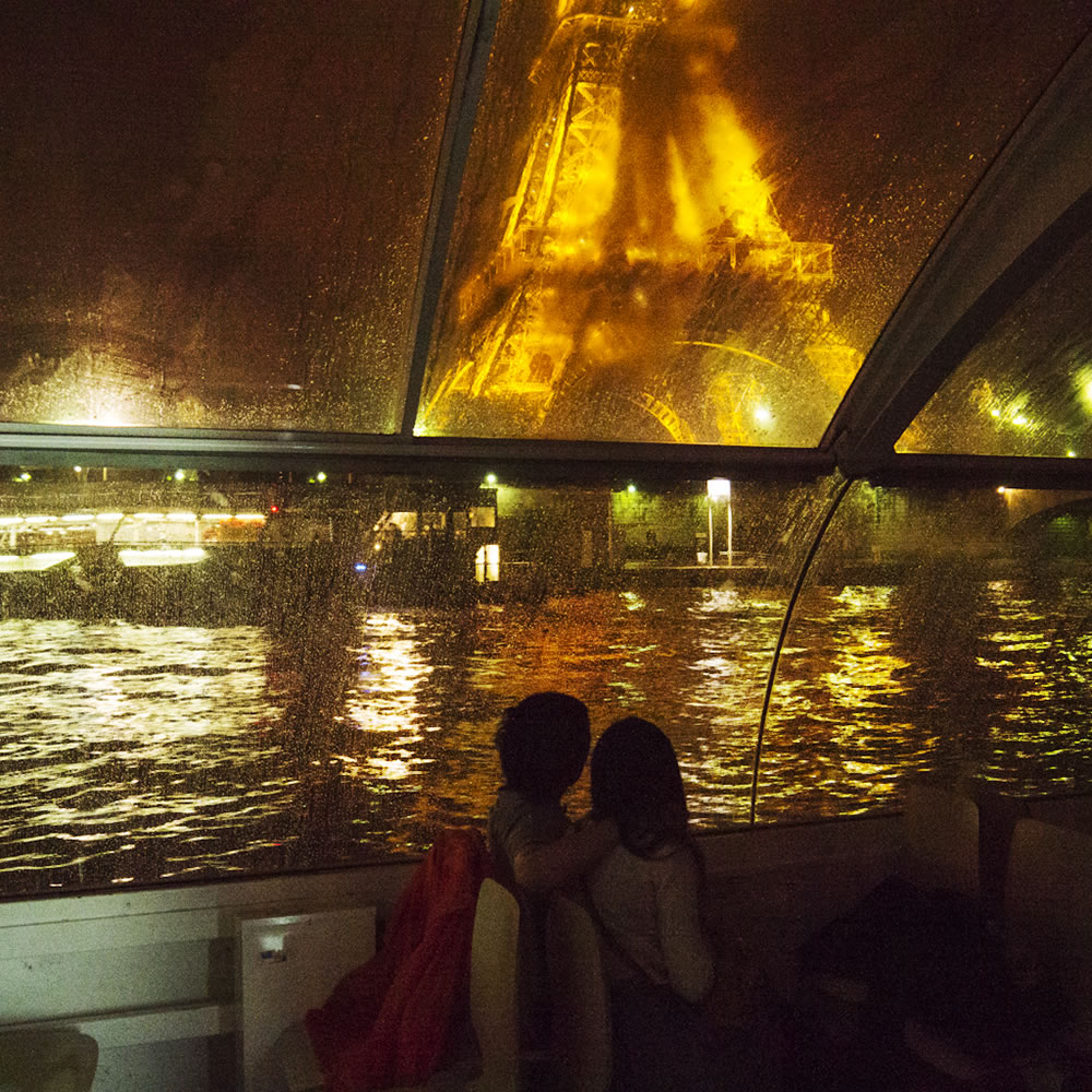 A rainy summer night from inside a Batobus (water-bus), cruising past the Eiffel Tower.