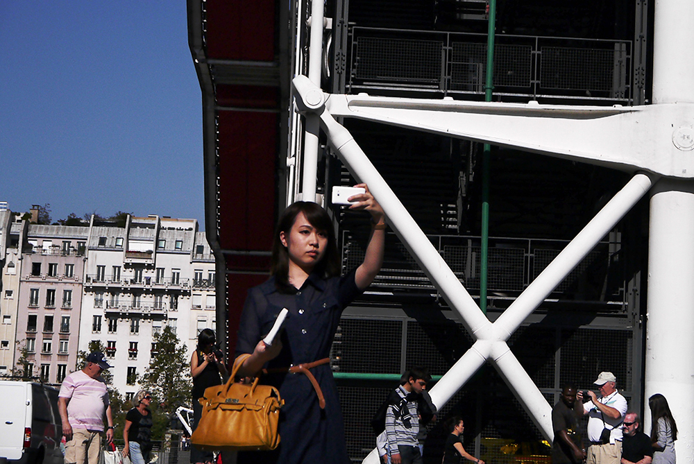 A woman photographing Niki de Saint Phalle's Stravinsky Fountain next to Centre Georges Pompidou, Paris.