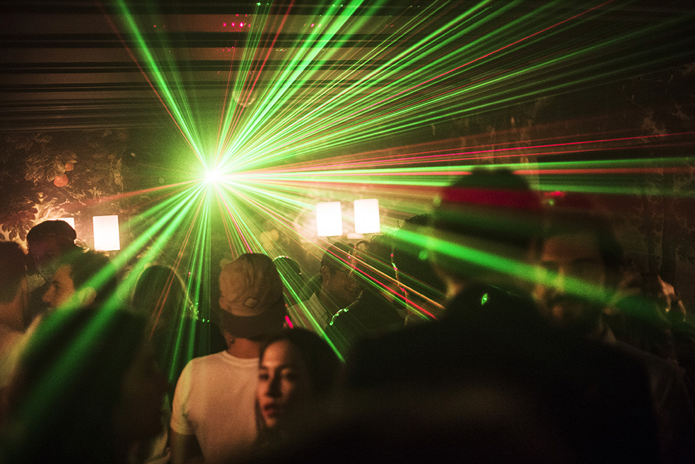 Laser light in the darkness of late-night insanity.  A night under ground in Montmartre, Paris.