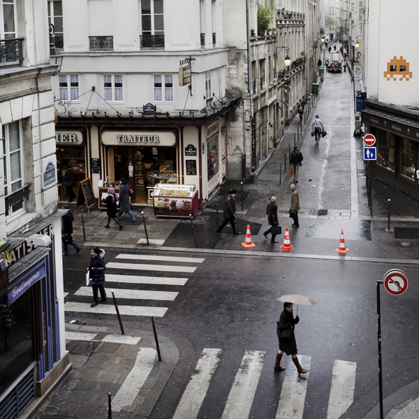 An Invader watches the rainy corner of rue Quincampoix and rue Rambuteau in central Paris.