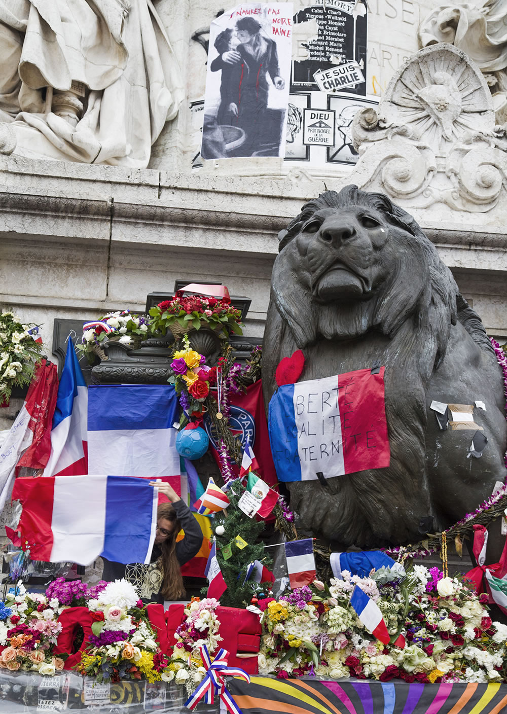 A young woman inspects a French flag on the collective memorial in the center of Place de la République, Paris.  The memorial was damaged on Sunday during conflict between police and protesters.