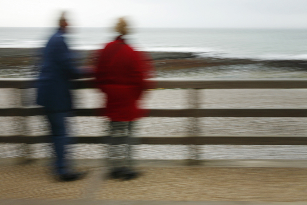 A couple visiting the Normandy coast in winter.