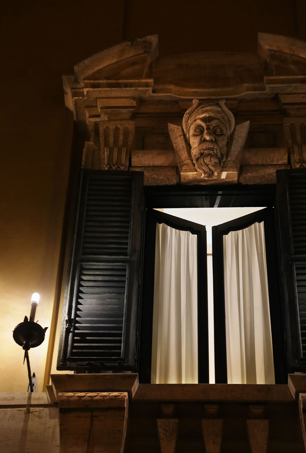 Standing guard over an open window in Rome.