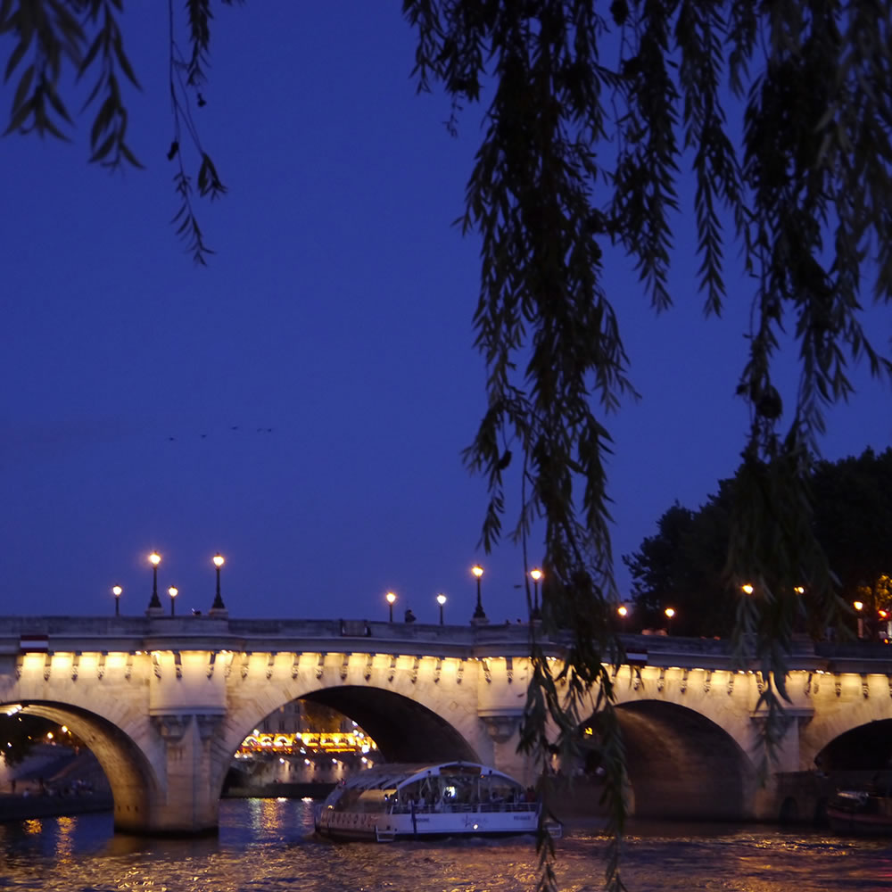 Under the weeping willow tree at the tip of Ile de la Cité, the brightly-lit cafés of Place St. Michel are visible through an arc in the Pont Neuf.