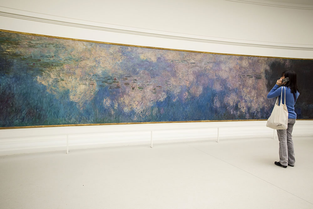 A girl listening to an audio guide in front of one of the 8 famous paintings of water lilies that Claude Monet had placed in the oval rooms in Paris's Orangerie. His choices were precise. He chose a building between the Seine river and the Tuileries Gardens. The rooms are oriented east-west, receiving the changing natural light via an open ceiling throughout the day. The painter wanted to create a meditative space to escape the world outside. Today there are long oval benches in the middle of the rooms, but it's most powerful to stand up close to the paintings.
