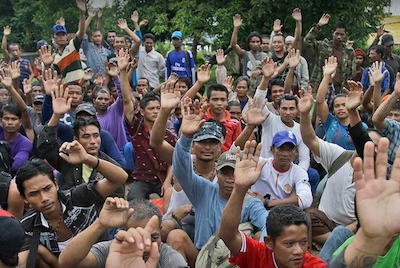 Rescued Burmese fishermen raise their hands as they are asked who among them wants to go home at the compound of Pusaka Benjina Resources fishing company in Benjina, Aru Islands, Indonesia, April 3, 2015. Photo by Dita Alangkara / AP