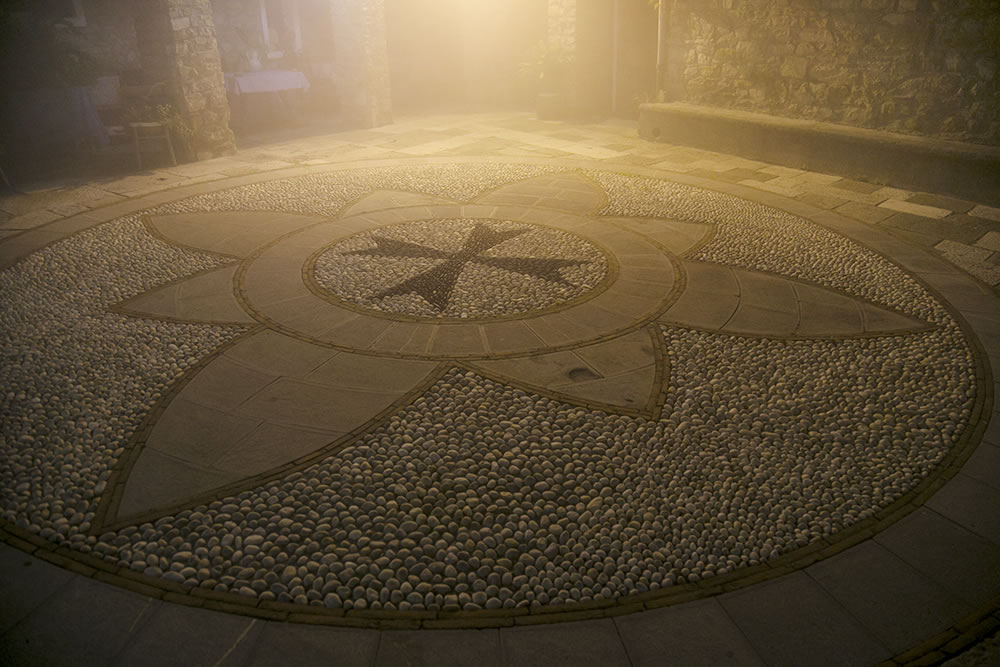 In the center of Seborga, Italy, on a night when the clouds surround the hilltop village and fill the streets with mist, we walk across the symbol of the Knights Templar, whose history in this independent state dates from the early 12th century.