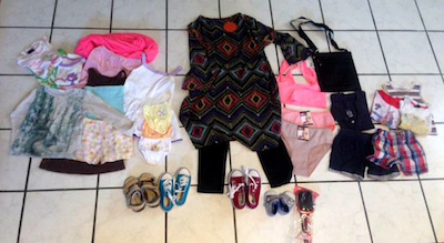 An example of what's inside a bag for a family with a mom and three kids. It's a mix of newly purchased and gently worn items. I've heard there's never enough underwear and that a purse is valuable because you can keep your most important things safe from theft. But those itty bitty baby shoes....squee! Photo by Marcy Franck.
