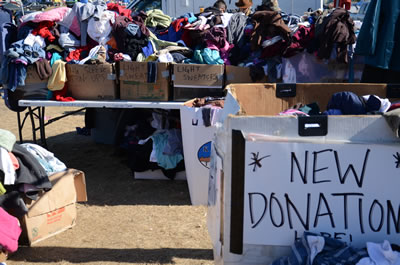 Overflowing boxes of donated winter clothes at Red Warrior Camp. Photo by Sven Jorgensen.