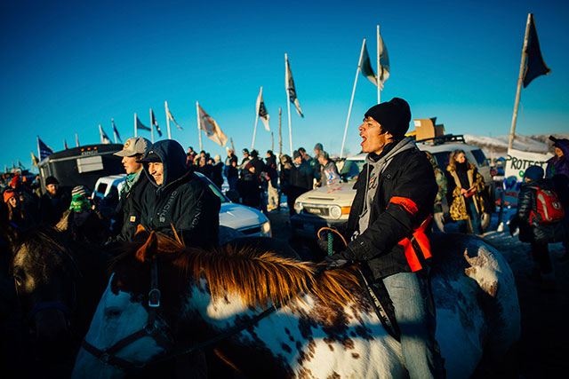 Atop his horse, Prophesy, JJ Stadel of the Cheyenne River Sioux of South Dakota celebrates after learning that permits would not be approved for a section of the Dakota Access pipeline, at the Oceti Sakowin protest camp, just outside the Standing Rock Sioux Reservation in Cannon Ball, North Dakota, December 4, 2016. (Photo: Alyssa Schukar / The New York Times)