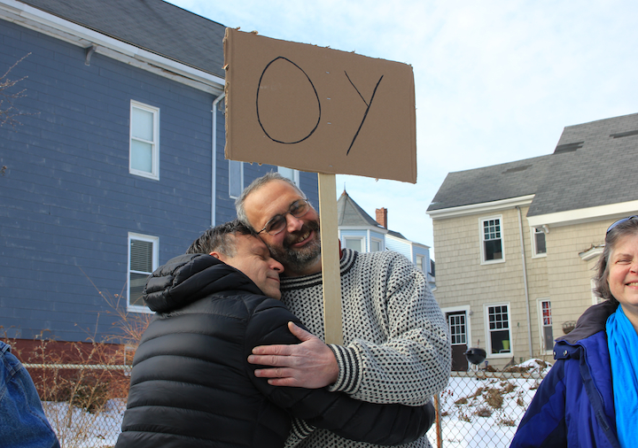 "My partner, Hal, shares some Yiddish love with the ""OY"" sign-holder. Photo by Amanda Painter."