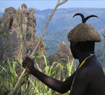 Member of Cameroon's Mofu tribe looking at a termite nest.