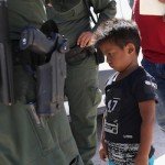 A boy from Honduras is shown being taken into custody by US Border Patrol agents near the US-Mexico Border near Mission, Texas, June 12, 2018. Photo by John Moore
