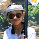 Boy in a funeral procession flashes the peace sign; the Balinese do not mind strangers witnessing their ceremonies. Karma and dharma are a strong part of their Hindu beliefs. Photo by Amanda Painter.